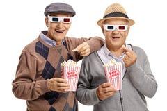 Dois homens idosos que vestem os vidros 3D e que comem a pipoca Imagens de Stock Royalty Free