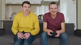 Dois homens jogam jogos de vídeo e riso video estoque