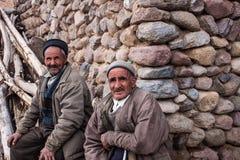 Dois homens locais sentam-se na frente de sua casa Imagens de Stock