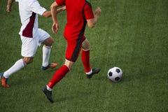 Dois homens lutam sobre o controle da bola durante um jogo de futebol imagem de stock