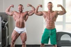 Dois homens musculares que dobram os músculos no Gym imagem de stock