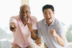 Dois homens na sala de visitas com de controle remoto Fotografia de Stock Royalty Free