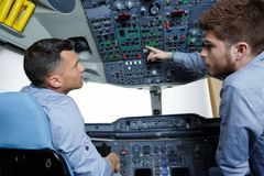 Dois homens no aprendiz da cabina do piloto de aviões que faz a pergunta foto de stock