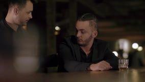 Dois homens nos ternos bebem o uísque em uma barra filme
