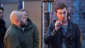 Dois homens novos bonitos estão estando exteriores, estão fumando e estão tendo a conversação video estoque