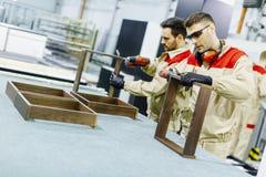 Dois homens novos consideráveis que trabalham na fábrica da mobília foto de stock