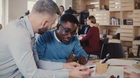 Dois homens novos felizes de raça misturada cooperam no projeto do negócio no escritório à moda na moda, riem, a seguir obtêm 4K  vídeos de arquivo