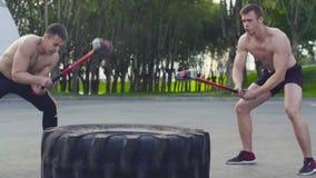 Dois homens novos que fazem exercícios em uma grandes roda e martelo filme
