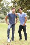 Dois homens novos que jogam com futebol no campo Foto de Stock Royalty Free