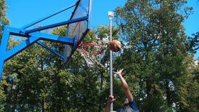 Dois homens novos que jogam o basquetebol no ar livre - um homem que joga a bola - outro marcar do homem filme