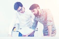 Dois homens novos que olham na folha de papel, tonificada Imagens de Stock