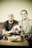 Dois homens novos que prestam atenção a um fósforo de futebol na tevê Imagem de Stock Royalty Free