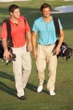 Dois homens que andam ao longo do campo de golfe fotografia de stock