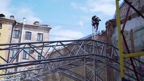 Dois homens que constroem trabalhadores no trabalho do uniforme e do capacete no auge da torre do PA vídeos de arquivo