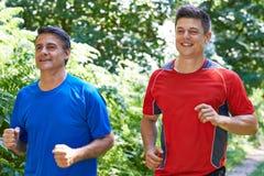 Dois homens que correm no campo junto Foto de Stock Royalty Free