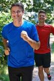 Dois homens que correm no campo junto Fotos de Stock