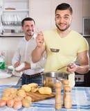 Dois homens que cozinham em casa Imagem de Stock Royalty Free