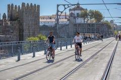 Dois homens que dão um ciclo em trilhas de estrada de ferro do metro no D Luis Bridge, parede medieval e monastério como o fundo foto de stock