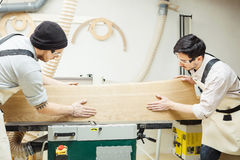 Dois homens que guardam a madeira na máquina do woodworking Imagem de Stock