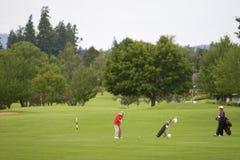 Dois homens que jogam o golfe - horizontal imagens de stock royalty free