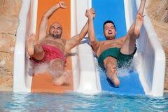 Dois homens que montam abaixo dos corrediça-amigos de uma água que apreciam um tubo da água montam Foto de Stock Royalty Free
