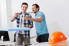 Dois homens que olham a rotação de velas da turbina eólica foto de stock royalty free