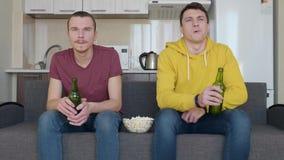 Dois homens que sentam-se no sofá olham um fósforo de futebol na tevê, cerveja da bebida e comem a pipoca video estoque