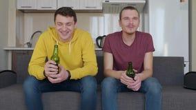 Dois homens que situam no sofá e para olhar um fósforo de futebol na tevê, na cerveja da bebida, no comentário e no sorriso video estoque