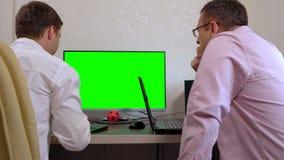 Dois homens que trabalham junto em computadores sincronizados vídeos de arquivo