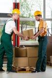 Dois homens que trabalham junto no armazém Foto de Stock