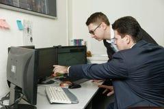 Dois homens que trabalham junto para os computadores no escritório contrataram na troca Foto de Stock Royalty Free