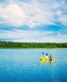 Dois homens remam um caiaque no lago Conceito do estilo de vida foto de stock royalty free