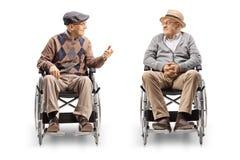 Dois homens superiores nas cadeiras de rodas que têm uma conversação imagem de stock
