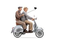 Dois homens superiores que montam em um 'trotinette' do vintage que toma um selfie com uma vara foto de stock