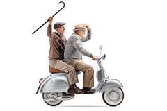 Dois homens superiores que montam um 'trotinette' do vintage e que acenam com um bastão imagem de stock