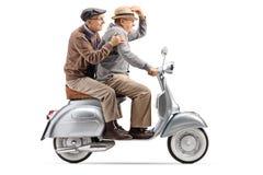 Dois homens superiores que montam um 'trotinette' do vintage rapidamente foto de stock royalty free