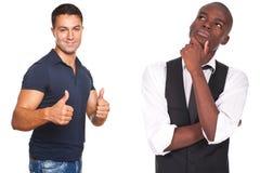 Dois homens, um pensando e outro com polegares acima Imagem de Stock Royalty Free