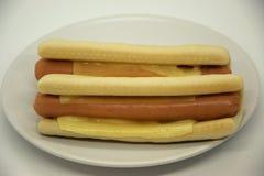 Dois hotdogs em uma placa branca em um fundo branco Fotos de Stock Royalty Free