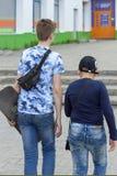 Dois indivíduos adolescentes andam abaixo da rua na cidade foto de stock