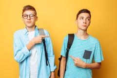 Dois indivíduos adolescentes apontam em se com seus polegares, culpa e não querem admitir sua culpa, isolada em um fundo amarelo foto de stock royalty free