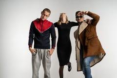 Dois indivíduos e menina na roupa colorida brilhante e escura ocasional à moda foto de stock royalty free