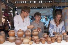 Dois indivíduos e uma menina que vende a cerâmica. Fotografia de Stock
