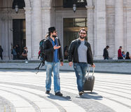 Dois indivíduos estão andando através das ruas de Genebra, Itália e estão olhando ao redor, falando entre si Foto de Stock Royalty Free