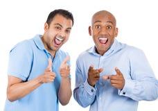 dois indivíduos frescos que apontam os dedos em você gesticulam e sorrir Foto de Stock