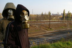 Dois indivíduos nas máscaras, estando de encontro a um contexto de Imagens de Stock