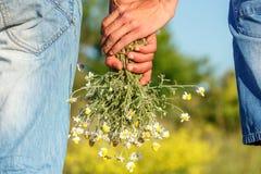Dois indivíduos que guardam as mãos com um ramalhete do conceito do relacionamento das flores fotografia de stock royalty free