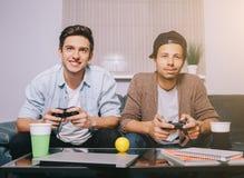 Dois indivíduos que jogam no console que senta-se no sofá Fotografia de Stock Royalty Free