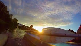 Dois indivíduos que kayaking no por do sol, esporte, câmera da ação, viajando video estoque