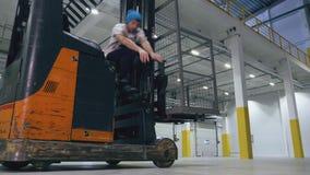 Dois indivíduos saltam sobre um caminhão do alcance em um centro logístico vazio video estoque