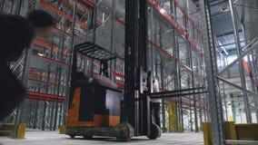 Dois indivíduos saltam sobre um caminhão do alcance em um centro logístico vazio Vista larga video estoque